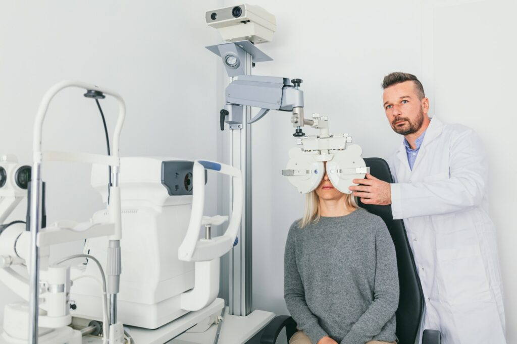 Eye doctor checking patient's eyes on a machine.